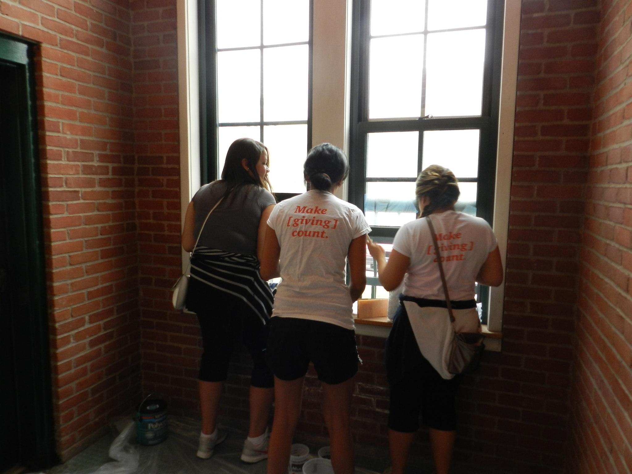 Volunteers from PricewaterhouseCoopers help refinish apartment furniture.